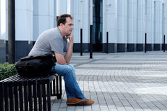 Sad man sitting in front of office building Royalty Free Stock Photo