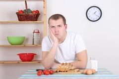 Sad man sitting in the kitchen Stock Image