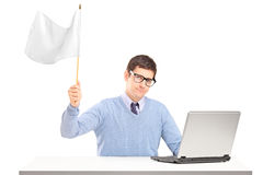Sad man sitting with laptop and holding a flag. Sad man sitting with laptop and holding a white flag gesturing defeat  on white background Royalty Free Stock Image