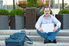 Sad man sitting on the steps with a suitcase Empty sign Stock Photo