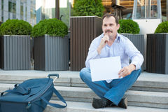 Sad man sitting on the steps with a suitcase Empty sign Royalty Free Stock Photo