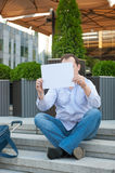 Sad man sitting on the steps with a suitcase Empty sign Stock Images
