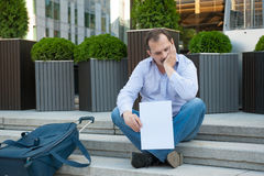 Sad man sitting on the steps with a suitcase Empty sign Royalty Free Stock Image