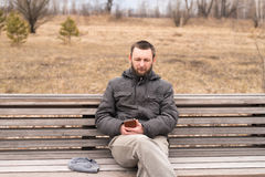 Sad man with smartphone on a bench Royalty Free Stock Images