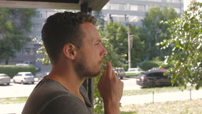 Sad man smokes on the terrace on a sunny day stock video