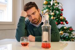 Lonely man celebrating christmas and drinking alone Royalty Free Stock Photography