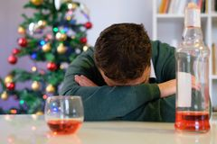 Sad man in solitude drinking alcohol all alone during christmas. Lonely man celebrating christmas and drinking alone Stock Image