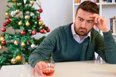 Sad man in solitude drinking alcohol alone. Lonely man celebrating christmas and drinking alone Royalty Free Stock Photos