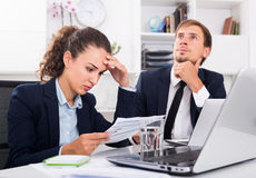 Sad man and sorrowful woman coworkers in firm office Stock Image