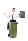 Sad man standing in a trash can Stock Image