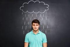 Sad man standing under the rain drawn on blackboard background Stock Photos