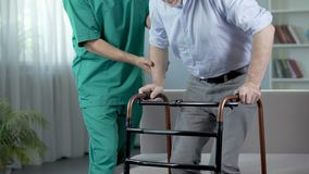 Sad man standing up and moving with walking frame at rehabilitation center