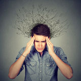 Sad man with stressed face expression brain melting into lines. Closeup sad young man with worried stressed face expression and brain melting into lines question Stock Images