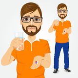 Sad man taking pills with glass of water. Portrait of young sad handsome hipster man with glasses taking pills with glass of water Royalty Free Stock Images