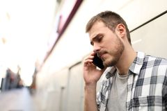 Sad man talking on phone in the street royalty free stock image