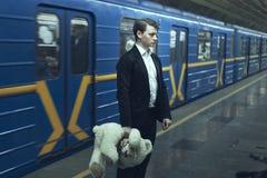 Sad man with a teddy bear in a subway. Sad man with a teddy bear in his hands standing in a subway station near train Stock Photos