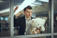 Sad man with a toy bear awaiting. Sad man with a toy bear waiting for a meeting. He looks out the window Royalty Free Stock Image