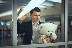 Sad man with a toy bear awaiting. Royalty Free Stock Image