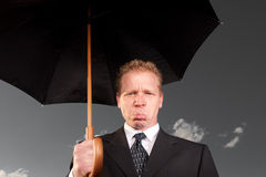 Sad man with umbrella. Sad man holds up umbrella with the background greyed out Royalty Free Stock Images