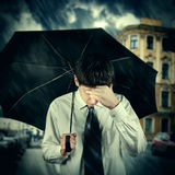 Sad Man under the Rain. Toned Photo of Sad Young Man with Umbrella under the Rain in the City Royalty Free Stock Photo