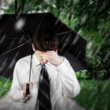 Sad Man under the Rain. Sad Young Man walk with Umbrella under the Rain in the Park royalty free stock images