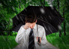 Sad Man under Rain. Sad Young Man walking with Umbrella under the Rain in the Summer Park Stock Photo