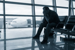 Sad man waiting for delayed flight. In airport Stock Image