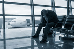 Sad man waiting for delayed flight. In airport Stock Images