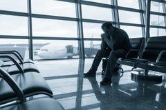 Sad man waiting for delayed flight Stock Photos