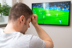 Sad man watching football. Stock Photo