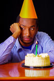 Sad man wearing blue shirt and hat sitting by table with cake in front, single candle burning, looking bored depressed Stock Photo