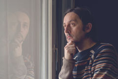 Sad man by the window Stock Images