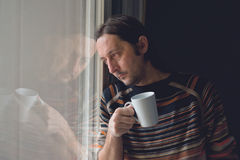 Sad man by the window drinking coffee Stock Image