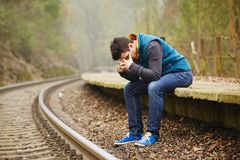 Sad man. Sad young man at the railway station royalty free stock photo