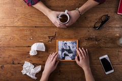 Sad mans, womans hands holding broken picture of romantic couple. Royalty Free Stock Photo