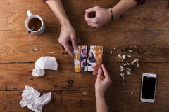 Sad mans, womans hands holding torn picture of romantic couple. Royalty Free Stock Image
