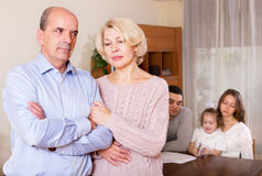 Sad mature couple and young parents with child Stock Photos
