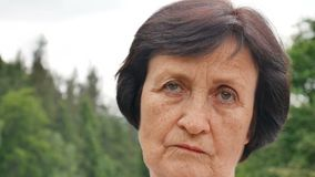 Sad mature lady with short dark hair and wrinkles on her face is looking at the camera on mountain hill with green. Forest background, HD stock video