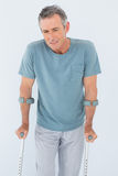 Sad mature man with crutches Royalty Free Stock Images