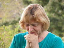 Sad Mature Woman. A sad, lonely, stressed mature woman fighting tears. Mental health concept Royalty Free Stock Photography