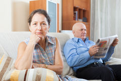 Sad mature woman against elderly man with newspaper Royalty Free Stock Images