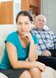 Sad mature woman against her husband Royalty Free Stock Photo