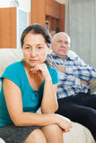 Sad mature woman against husband at home Royalty Free Stock Images