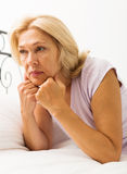 Sad mature woman. With head reclined upon hands in bed at bedroom Stock Photo