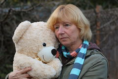 Sad mature woman hugging plush bear Royalty Free Stock Images