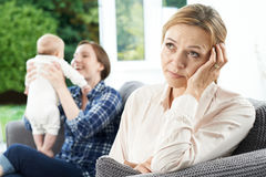Sad Mature Woman Jealous Of Mother With Young Baby Royalty Free Stock Photos