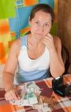 Sad mature woman with money. Portrait of sad mature woman with money  at home Royalty Free Stock Photos