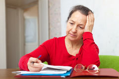 Sad mature woman reads documents. At home Stock Photography