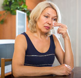 Sad mature  woman sitting on chair Royalty Free Stock Image