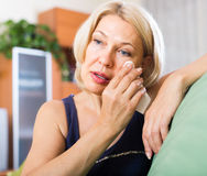 Sad  mature woman sitting on couch Royalty Free Stock Image
